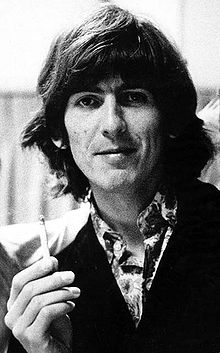 Black-and-white shot of George, in his 20s, with long, dark hair.